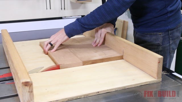 cutting a step stool top to size on a table saw cross cut sled