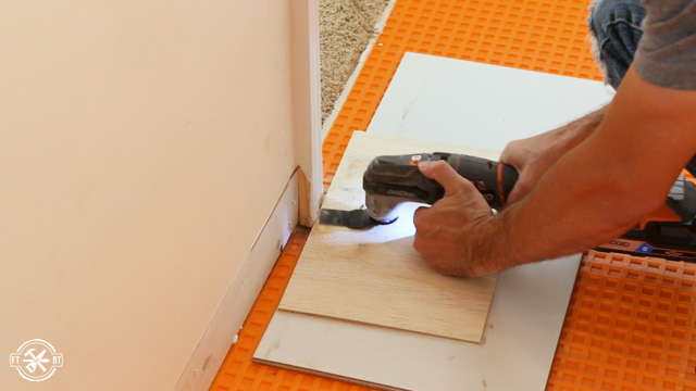 using a multitool to cut back door frames for room for tiles