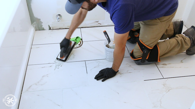 grouting the tiles in the bathroom floor