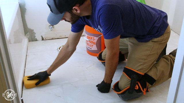 wiping excess grout off of tiles with a wet sponge