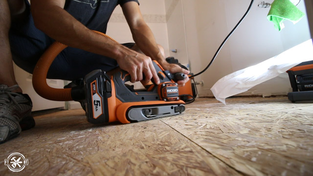 smoothing out floor with belt sander
