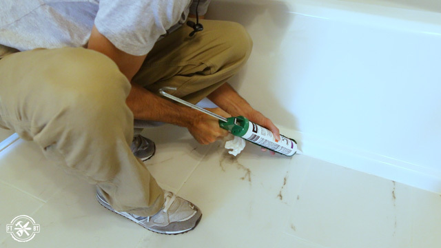 applying grout colored caulk in front of the bathtub