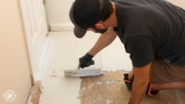 spreading mortar on bathroom floor