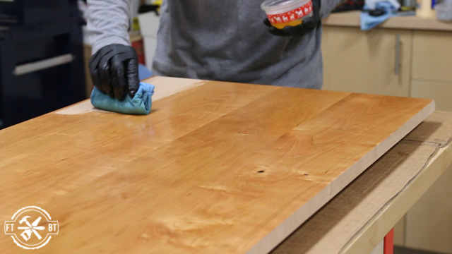 applying a coat of oil based polyurethane to wood