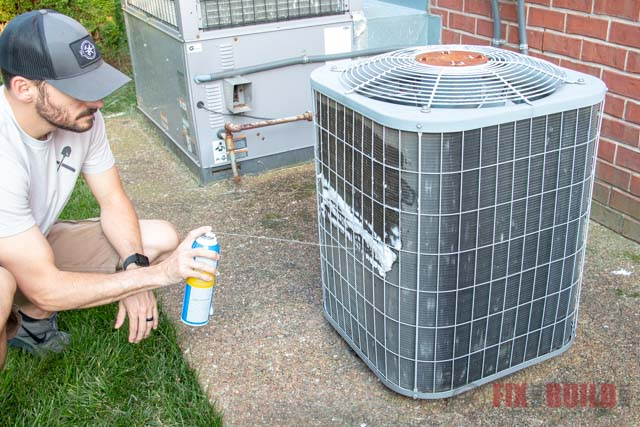 spraying air conditioner cleaner on AC unit