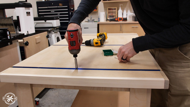 screwing down the t-track to the table saw outfeed table