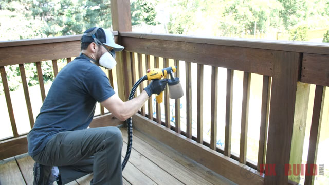 spraying spindles on deck with stain