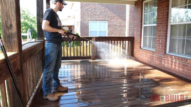 spraying cleaner on deck