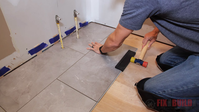 tapping vinyl plank flooring into place