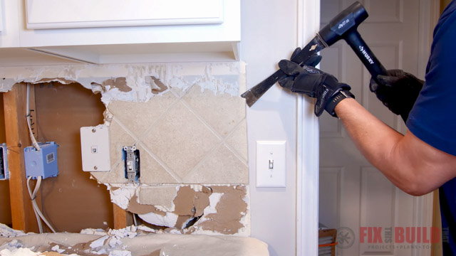 removing tile with pry bar and mallet