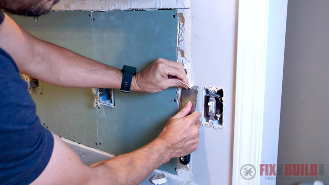 trimming drywall seam with knife