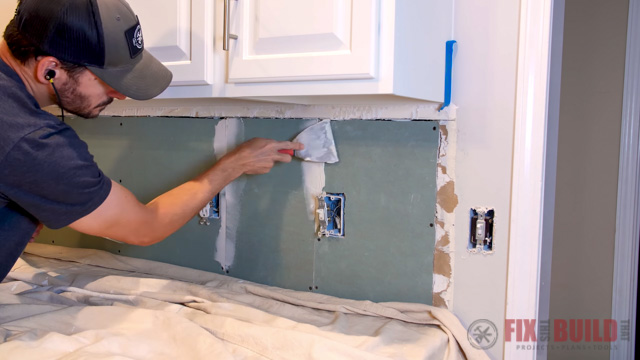 applying tile adhesive to drywall joints